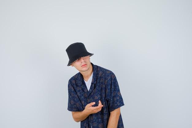 Młody chłopak wyciągający rękę, trzymając coś wyimaginowanego w białej koszulce, kwiecistej koszuli, czapce i wyglądający na pewnego siebie, widok z przodu.