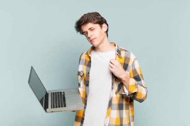 Młody chłopak wyglądający arogancko, odnoszący sukcesy, pozytywny i dumny, wskazujący na siebie
