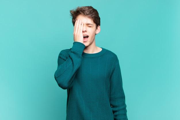 Młody chłopak wyglądający na zaspanego, znudzonego i ziewającego, z bólem głowy i jedną ręką zakrywającą połowę twarzy
