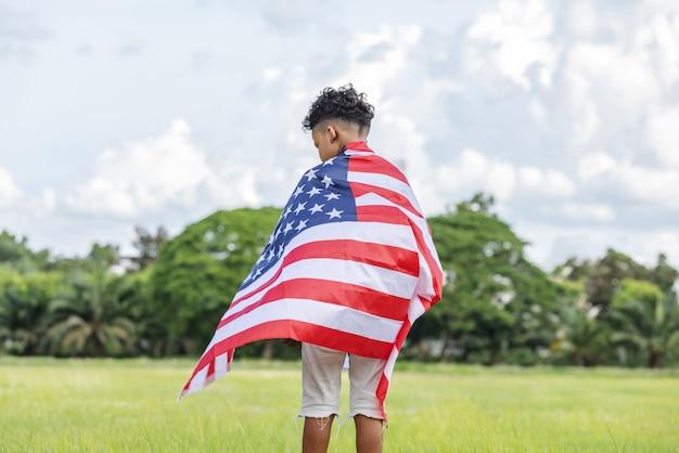Młody chłopak z amerykańską flagą usa świętuje 4 lipca