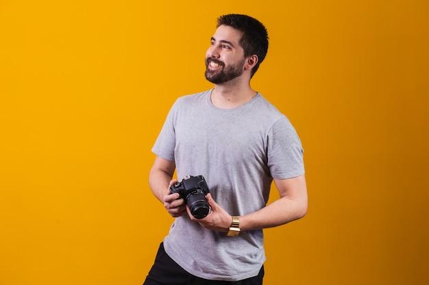 Młody chłopak z aparatem fotograficznym w ręku. piękny fotograf na żółtym tle