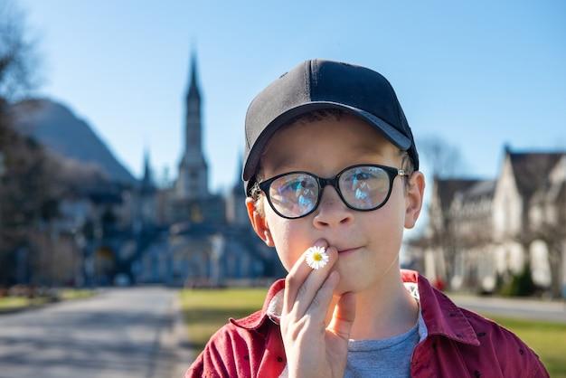 Młody chłopak z bazyliką w lourdes we francji