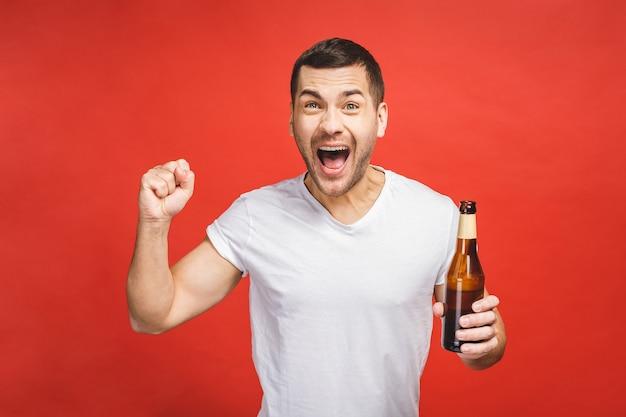 Młody chłopak z brodą na białym tle na czerwonym tle trzyma butelkę piwa