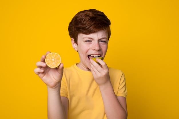 Młody chłopak z czerwonymi włosami, jedzenie pokrojonej cytryny na żółtej ścianie studia
