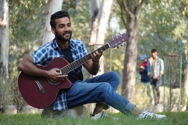 Młody chłopak z gitarą i gra na gitarze w parku