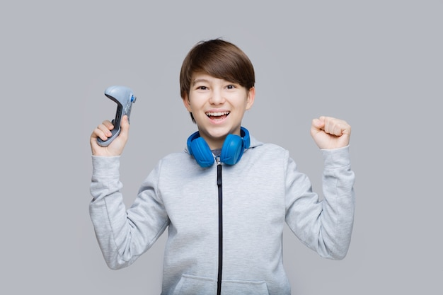 Młody chłopak z joystickiem w rękach grający w gry wideo