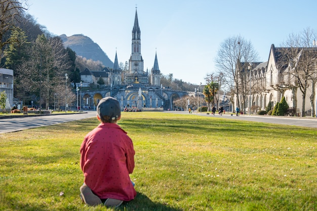 Młody chłopak z katedrą-sanktuarium w lourdes (francja)