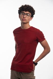 Młody chłopak z kręconymi włosami w okularach.