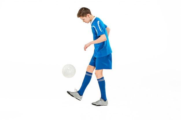 Młody chłopak z piłki nożnej robi kopnięcie latające