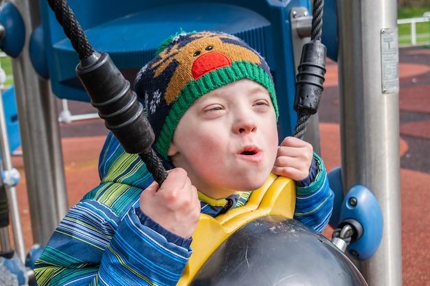 Młody chłopak z zespołem downa, który bawi się na placu zabaw