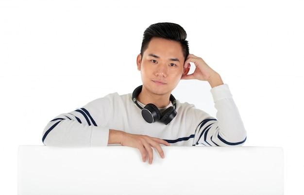 Młody chłopak z zestawem słuchawkowym o zamyślonym spojrzeniu, oparty o ściankę działową