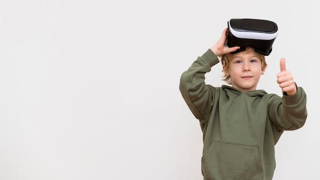 Młody chłopak za pomocą zestawu słuchawkowego wirtualnej rzeczywistości i pokazując kciuki do góry