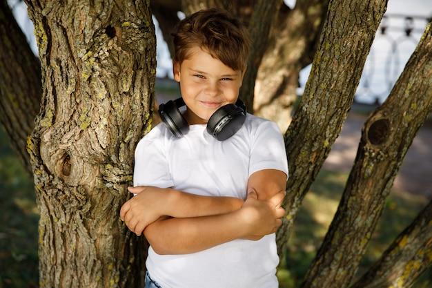 Młody chłopak ze słuchawkami stoi w parku