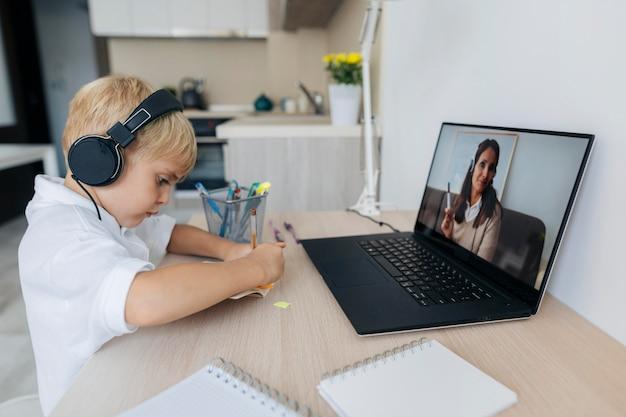 Młody chłopak, zwracając uwagę na zajęcia online