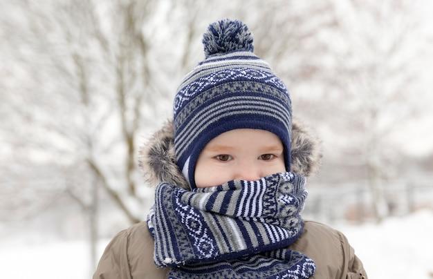 Młody chłopiec dziecko idąc ulicą, zbliżenie w zimie