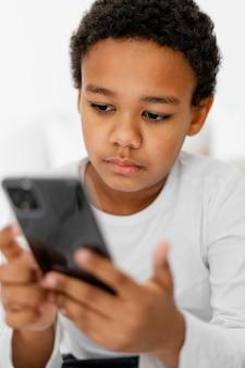 Młody chłopiec dziecko za pomocą telefonu komórkowego