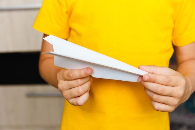Młody chłopiec dziecko zachować białą papierową muchę w ręce w żółtym t-krótkim zbliżenie