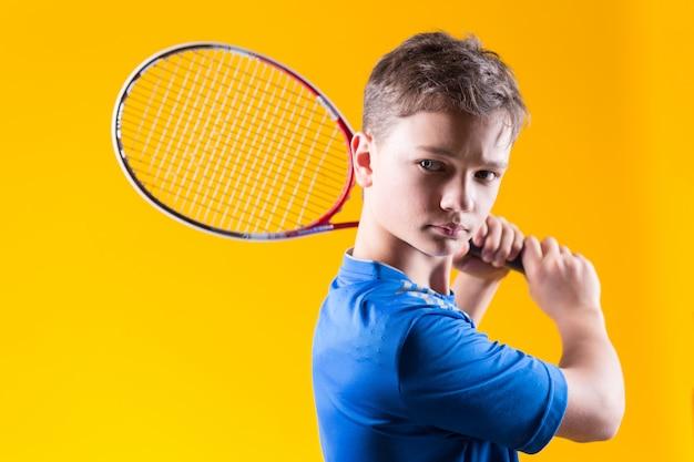 Młody chłopiec gracz w tenisa na jaskrawej kolor żółty ścianie