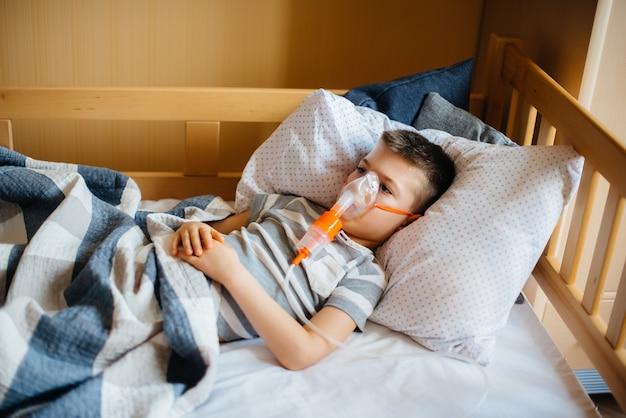 Młody chłopiec otrzymuje inhalację podczas choroby płuc. medycyna i opieka