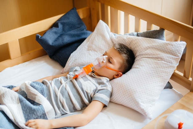 Młody chłopiec otrzymuje inhalację podczas choroby płuc. medycyna i opieka.