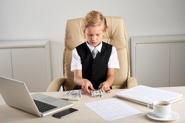 Młody chłopiec rasy białej siedzi w fotelu wykonawczym w biurze i liczenia dolarów na biurku