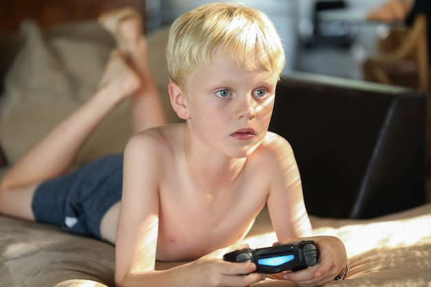 Młody chłopiec rasy kaukaskiej grający w gry wideo w domu na kanapie w miękkim popołudniowym świetle