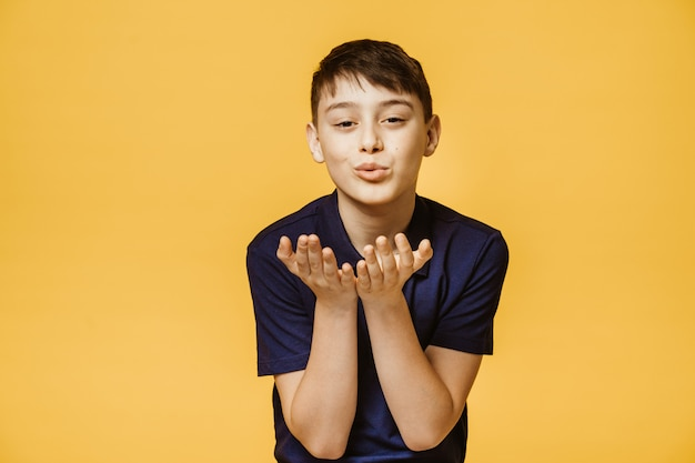 Młody chłopiec rasy kaukaskiej pokazuje jej dobre samopoczucie, żegna się z odległości, izolowany na żółtej ścianie. model młodego chłopca sprawia, że pocałunek powietrza.