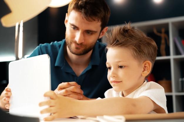 Młody chłopiec siedzi z ojcem przy stole i za pomocą laptopa