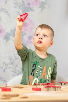 Młody chłopiec trzyma w dłoni kształt piernika, wyciągając go pod światło.