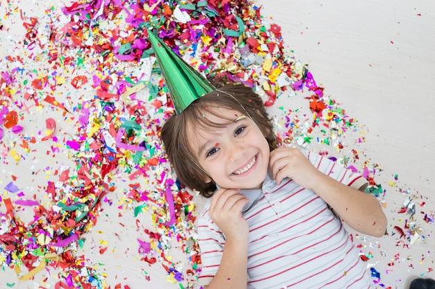 Młody chłopiec wydmuchuje out confetti, odizolowywających na białym tle