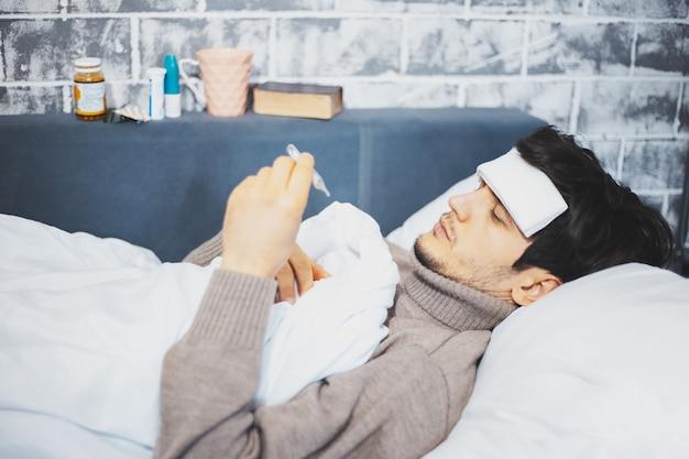 Młody chory człowiek leżący na łóżku trzymając w ręku termometr na ścianie innych leków.