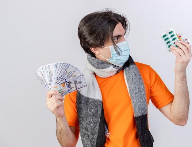 Młody chory człowiek ubrany w szalik i maskę medyczną, trzymając gotówkę i patrząc na pigułki w ręku na białym tle