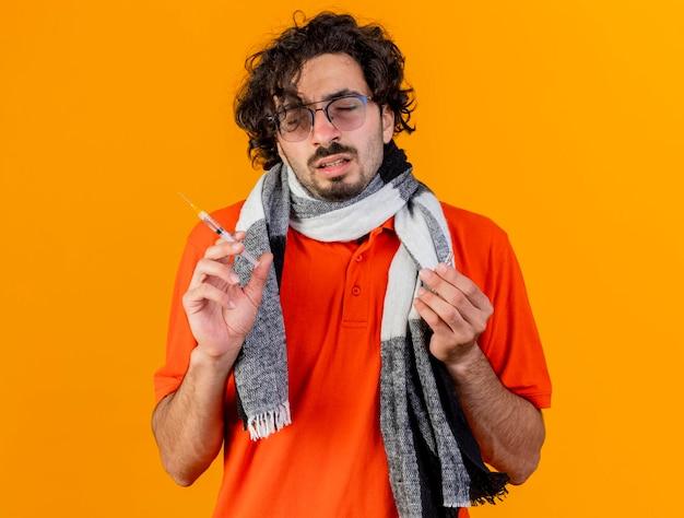 Młody chory człowiek w okularach i szalik trzymając strzykawkę i ampułkę z zamkniętymi oczami na białym tle na pomarańczowej ścianie