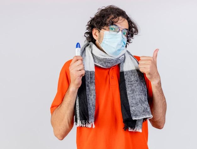 Młody chory człowiek w okularach szalik i maska trzyma termometr patrząc z przodu pokazując kciuk do góry na białym tle na białej ścianie