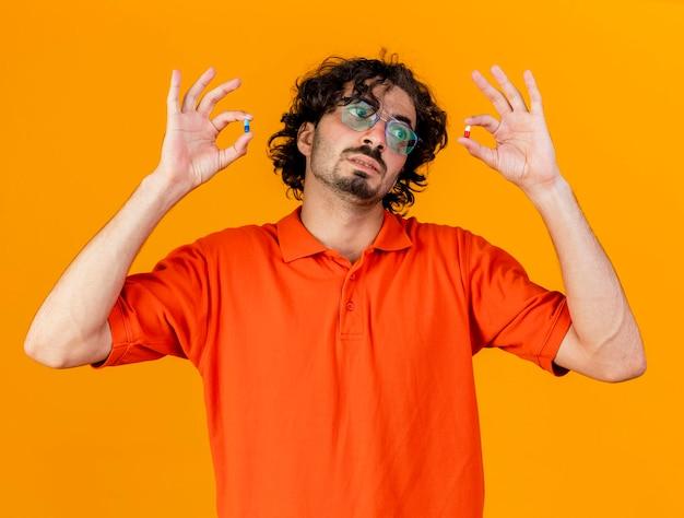 Młody chory człowiek w okularach, trzymając i patrząc na kapsułki medyczne na białym tle na pomarańczowej ścianie