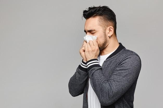 Młody chory człowiek z zasmarkanym nosem, temperaturą i złym samopoczuciem. chory kichnął