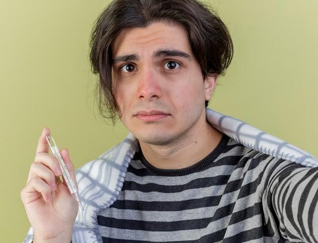 Młody chory człowiek zawinięty w kratę, trzymając termometr z aparatem na białym tle na oliwkową zieleń