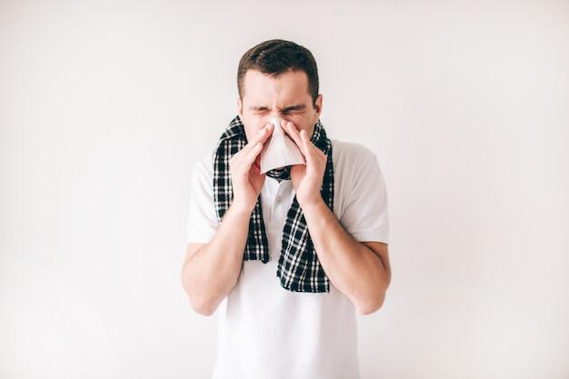 Młody chory mężczyzna odizolowywający nad biel ścianą. facet kicha do białej serwetki. chora osoba sama z szalikiem na szyi