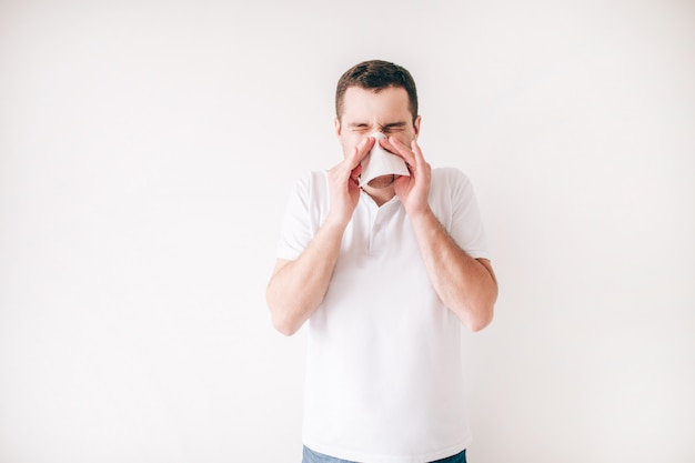 Młody chory mężczyzna odizolowywający nad biel ścianą. samodzielny kichanie w białą tkankę. chory chory cierpi na chorobę.