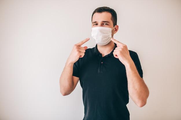 Młody chory mężczyzna odizolowywający nad ścianą. facet w czarnej koszuli nosić maskę ochronną. wskazują na to prawdopodobnie chorzy chorzy.