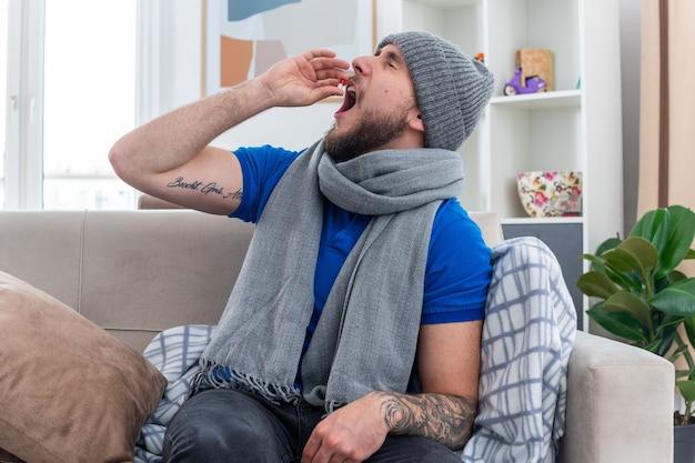 Młody chory mężczyzna ubrany w szalik i czapkę zimową, siedzący na kanapie w salonie, biorący kapsułkę medyczną z zamkniętymi oczami