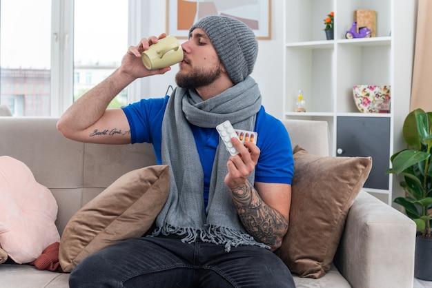 Młody chory mężczyzna ubrany w szalik i czapkę zimową siedzący na kanapie w salonie, trzymający paczki leków medycznych popijający filiżankę herbaty