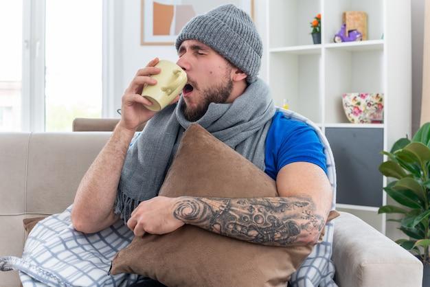 Młody chory mężczyzna ubrany w szalik i zimową czapkę owinięty w koc, siedzący na kanapie w salonie, trzymający poduszkę pijącą leki z kubka z zamkniętymi oczami