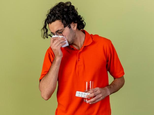 Młody chory mężczyzna w okularach trzyma szklankę wody i paczkę tabletek medycznych wycierając nos serwetką odizolowaną na oliwkowej ścianie z miejscem na kopię
