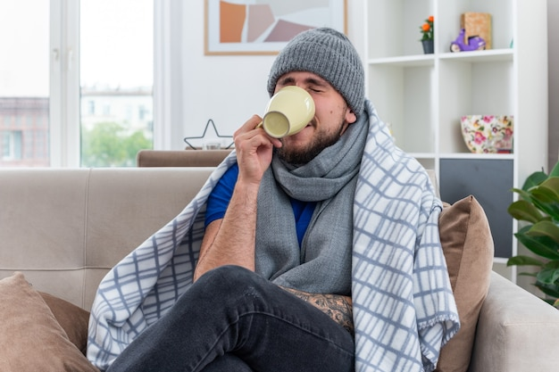 Młody chory mężczyzna w szaliku i czapce zimowej siedzący na kanapie w salonie owinięty kocem, pijący herbatę z zamkniętymi oczami