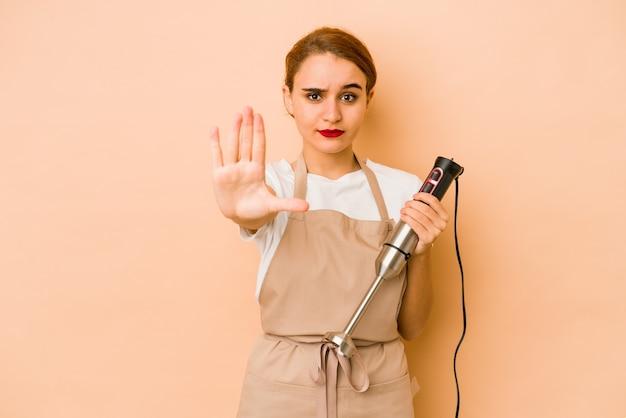 Młody chudy kucharz arabski kobieta stojąca z wyciągniętą ręką pokazujący znak stopu, uniemożliwiając ci.