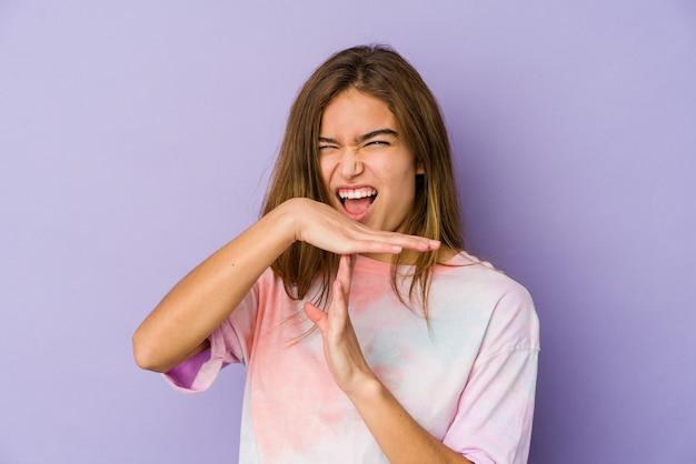 Młody chudy nastolatek kaukaski dziewczyna na fioletowo pokazujący gest limitu czasu.