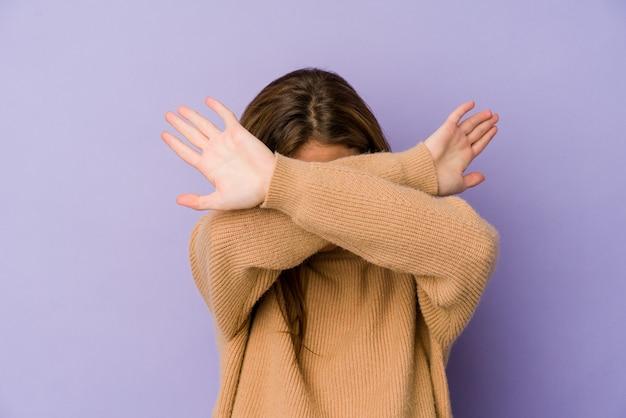 Młody chudy nastolatek kaukaski dziewczyna na fioletowo trzymając dwie skrzyżowane ręce, koncepcja odmowy.