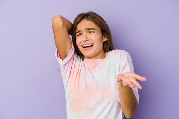 Młody chudy nastolatek kaukaski dziewczyna na fioletowym tle krzyczy z wściekłości.