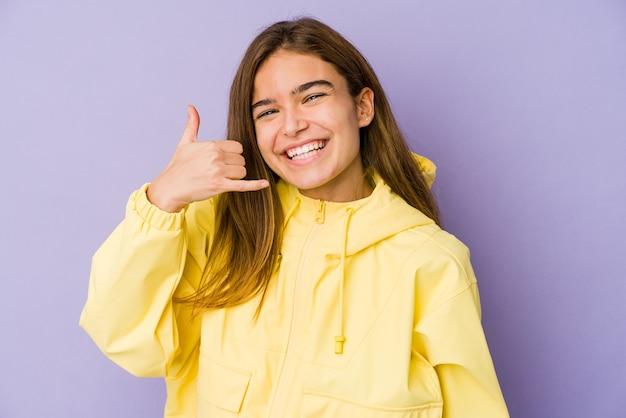 Młody chudy nastolatek kaukaski dziewczyna na fioletowym tle pokazujący gest rozmowy telefonicznej palcami.